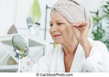 a-senior-woman-plucking-her-eyebrows-wit
